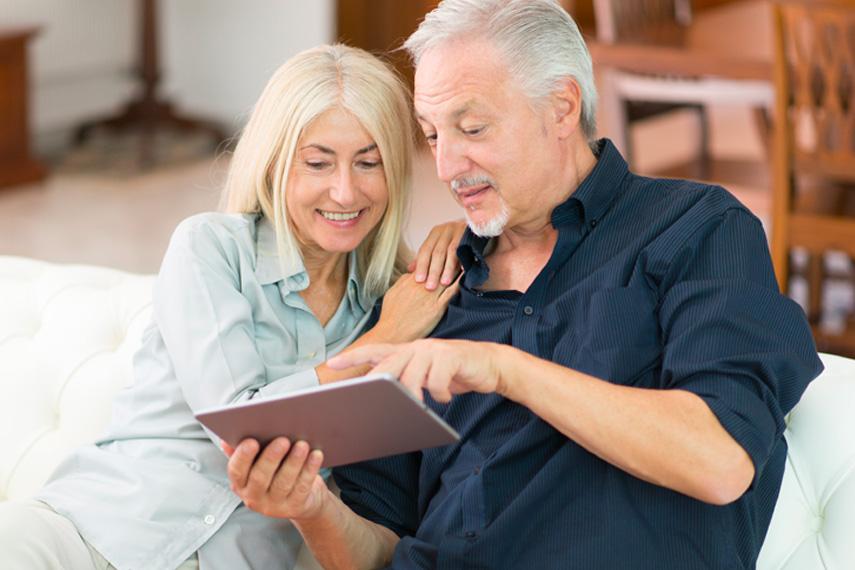 Coppia consulta il tablet sul divano della loro casa