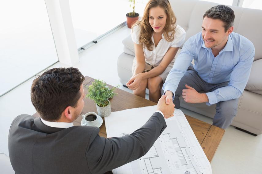 Agente immobiliare stringe la mando ad una giovane coppia