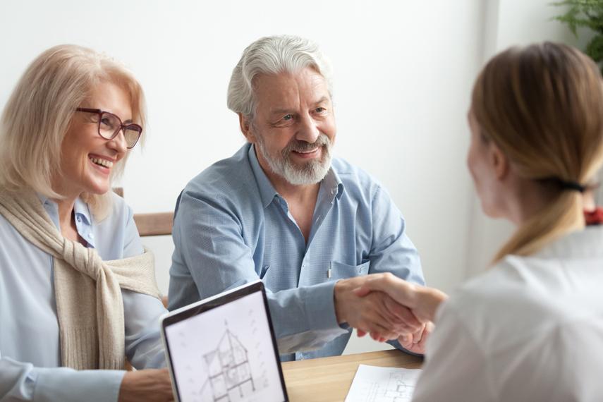 Coppia senior e agente immobiliare in ufficio