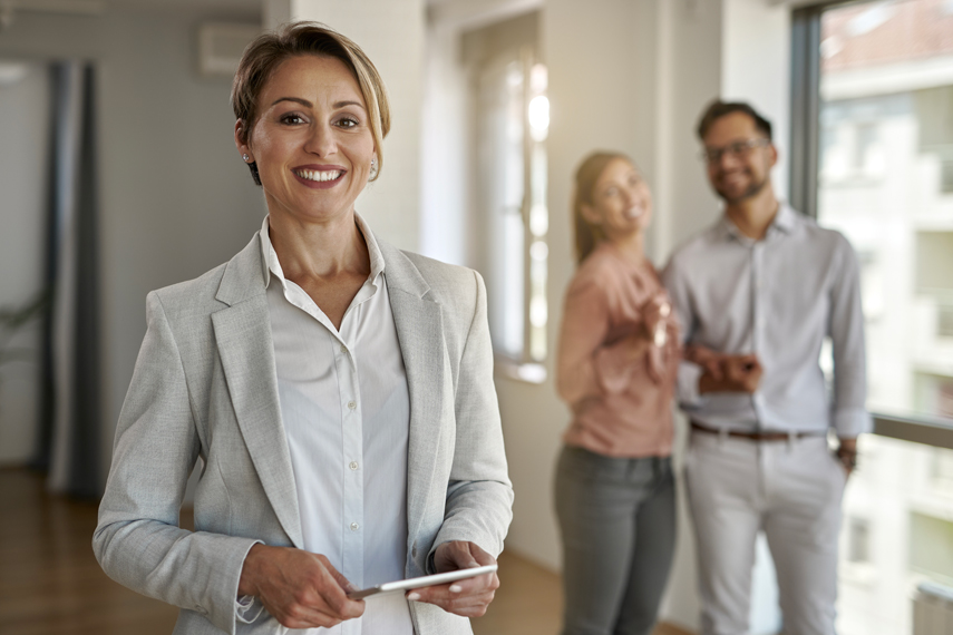 Agente immobiliare in un appartamento con alcuni clienti