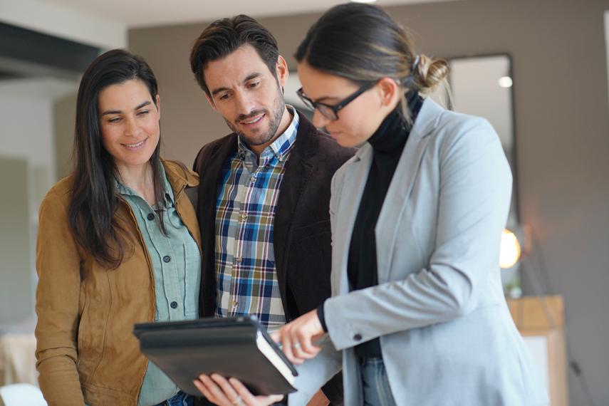 Agente immobiliare con alcuni clienti in un appartamento