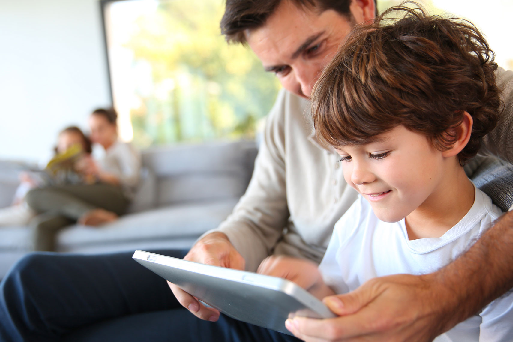 Padre e figlio sul divano guardano il tablet